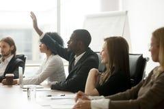 Afrykańska biznesmena dźwigania ręka pyta pytanie przy różnorodną drużyną Fotografia Royalty Free