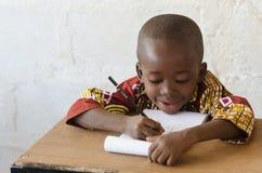 Afrykańska czarna chłopiec przy Szkolnym Writing z kopii przestrzenią Fotografia Royalty Free