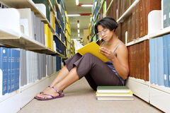 Afrykańska dziewczyna czyta książkowego obsiadanie na bibliotecznej podłoga Fotografia Royalty Free