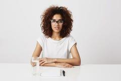 Afrykańska dziewczyna patrzeje kamerę siedzi nad białym tłem w szkłach kosmos kopii fotografia stock