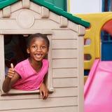 Afrykańska dziewczyna w domek do zabaw mienia aprobatach Fotografia Stock