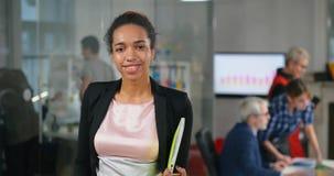 Afrykańska kierownik pozycja i ono uśmiecha się w biurze patrzeje kamerę zbiory