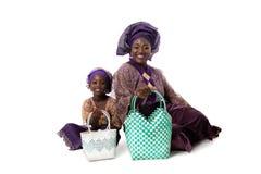 Afrykańska kobieta i mała dziewczynka w tradycyjnej odzieży z duży ciężar torbami odosobniony Zdjęcie Royalty Free
