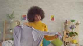 Afrykańska kobieta próbuje na z afro fryzurą odziewa przed lustrem w jego nowożytnym mieszkaniu wolny mo zbiory wideo