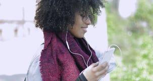 Afrykańska kobieta z hełmofonami i telefonu pozować zbiory