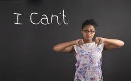 Afrykańska kobieta z kciukami zestrzela ręka sygnał no Mogę na blackboard tle Fotografia Royalty Free