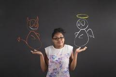 Afrykańska kobieta z no znam anioła i czarciego gesta na blackboard tle Zdjęcie Royalty Free