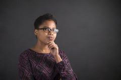 Afrykańska kobieta z ręką na podbródka główkowaniu na blackboard tle Zdjęcie Stock