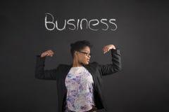 Afrykańska kobieta z silnymi rękami dla biznesu na blackboard tle zdjęcia stock
