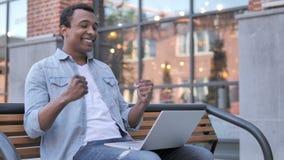 Afrykańska mężczyzna odświętność na laptopu obsiadaniu Na zewnątrz biura zdjęcie wideo