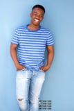 Afrykańska męska młodość ono uśmiecha się przeciw błękit ścianie Zdjęcia Stock