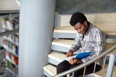 Afrykańska studencka chłopiec lub mężczyzna czytelnicza książka przy biblioteką obraz stock