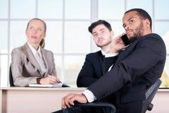 Afrykański biznesmen opowiada na jego telefonie komórkowym Trzy pomyślny Zdjęcie Stock