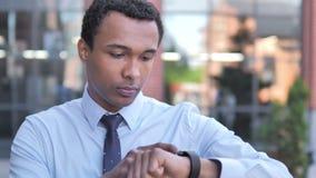 Afrykański biznesmen używa smartwatch plenerowego zbiory