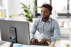 Afrykański biznesmen z komputerem przy biurem zdjęcie stock