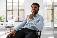Afrykański biznesmena obsiadanie na biurowym krześle obraz royalty free