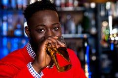 Afrykański facet pije piwo, plamy tło Obrazy Royalty Free