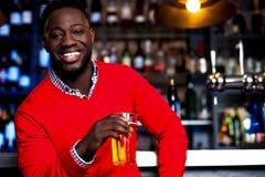 Afrykański facet pozuje z zazębionym piwem obraz stock
