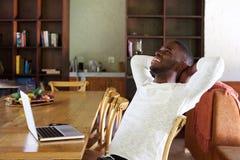 Afrykański facet relaksuje w domu z laptopem na stole fotografia stock