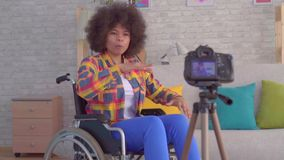 Afrykański kobiety blogger obezwładniający w wózku inwalidzkim z afro fryzurą nagrywa wideo obsiadanie przed kamerą zbiory