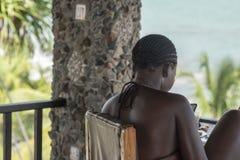 Afrykański kobiety obsiadanie z telefonem fotografia royalty free