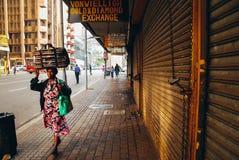 Afrykański kobiety odprowadzenie w mieście z bagażem na jej głowie obraz royalty free
