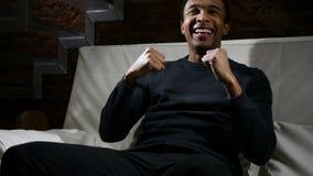 Afrykański mężczyzna dopatrywania dopasowanie na TV i odświętność Zespalamy się sukces zbiory wideo