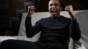 Afrykański mężczyzna dopatrywania dopasowanie na TV i odświętność Zespalamy się sukces zdjęcie stock