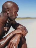 Afrykański mężczyzna jest ubranym słuchawki siedzi samotnie Zdjęcia Royalty Free
