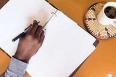 Afrykański mężczyzna mienia pióro w ręce pisać na pustym białym papierze obrazy royalty free
