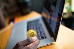 Afrykański mężczyzna mienie w ręka symbolu bitcoin crypto waluta - elektroniczny wirtualny pieniądze dla sieci bankowości na lapt fotografia royalty free