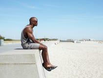 Afrykański mężczyzna obsiadanie na plażowym deptaku Zdjęcie Royalty Free