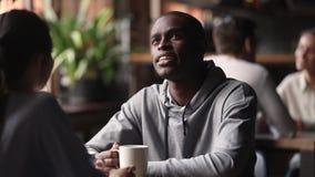 Afrykański mężczyzna pije herbaty opowiada caucasian kobieta przy spotkaniem zbiory wideo