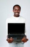 Afrykański mężczyzna pokazuje pustego laptopu ekran fotografia stock