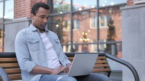 Afrykański mężczyzna pracuje na laptopie, Siedzi na ławce zbiory wideo