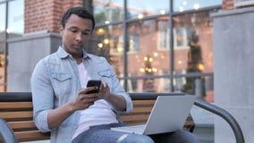Afrykański mężczyzna Używa Smartphone i laptop Siedzi na ławce, zdjęcie wideo