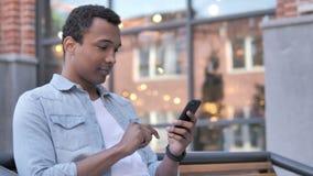 Afrykański mężczyzna używa smartphone siedzieć plenerowy zbiory wideo