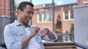 Afrykański mężczyzna Używa Smartwatch Siedzieć Plenerowy zbiory