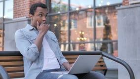 Afrykański mężczyzna w szoku podczas gdy Pracujący na laptopie Plenerowym zbiory wideo