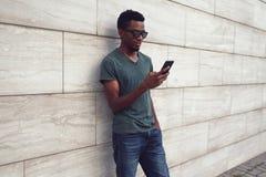 afrykański mężczyzna z smartphone na miasto ulicie, szara ściana z cegieł zdjęcia stock
