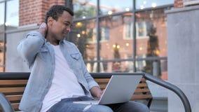Afrykański mężczyzna z szyja bólem Używać laptop Plenerowego zdjęcie wideo