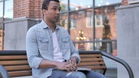 Afrykański mężczyzny przybycie, obsiadanie na ławce używać laptop i zbiory wideo