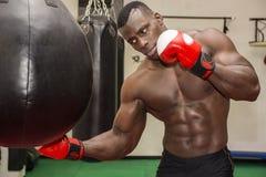 Afrykański męski bokser uderza pięścią piłkę jest ubranym boksować Obrazy Royalty Free