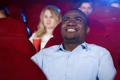 Afrykański męski widz ogląda ciekawego film w kinie obrazy stock