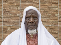 Afrykański starego człowieka obsiadanie przed jego domem, osiemdziesiąt lat Fotografia Stock