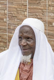 Afrykański starego człowieka obsiadanie przed jego domem, osiemdziesiąt lat Fotografia Royalty Free