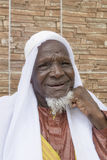 Afrykański starego człowieka obsiadanie przed jego domem, osiemdziesiąt lat Zdjęcia Stock