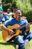 Afrykański student collegu bawić się gitarę Obraz Royalty Free