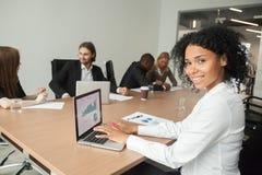 Afrykański uśmiechnięty bizneswoman patrzeje kamerę używać laptop przy Zdjęcie Royalty Free
