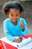 Afrykański uczeń robi aprobatom przy stołem Obrazy Royalty Free